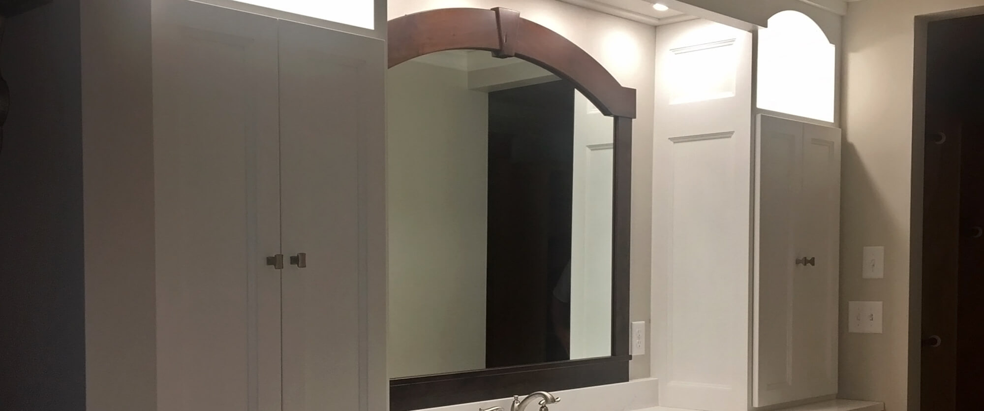 Custom bath vanity featuring upper solid wood cabinets, lighted display boxes, and a framed mirror; designed, built, and installed by finewood Structures of Browerville, MN