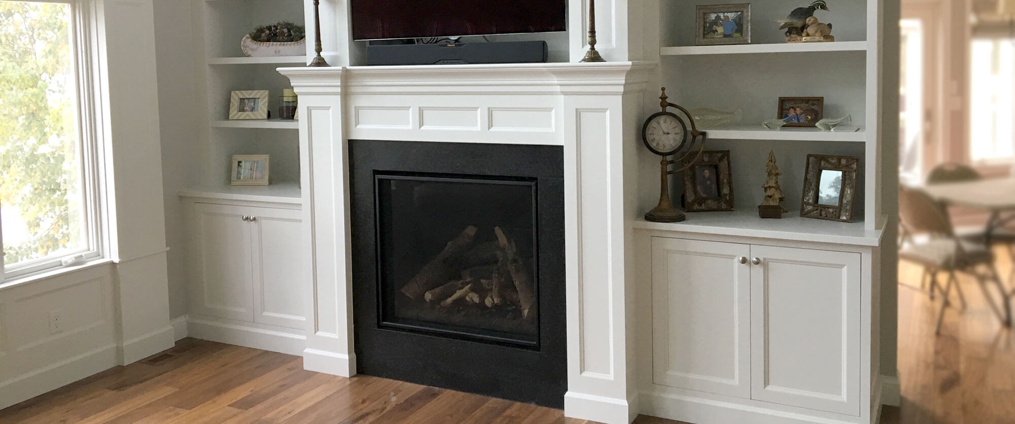Custom fireplace surround with built in shelving on either side made of solid wood and painted white; designed, built, and installed by finewood Structures of Browerville, MN