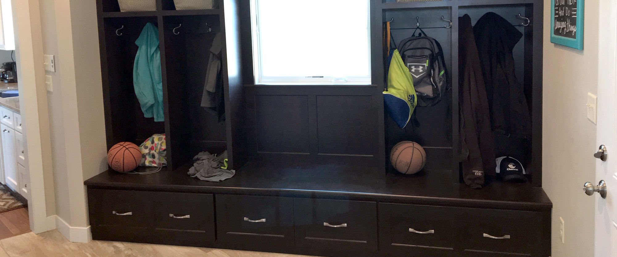 Custom entryway mudroom locker with jacket hooks, a seating bench, and under bench storage; designed, built, and installed by finewood Structures of Browerville, MN